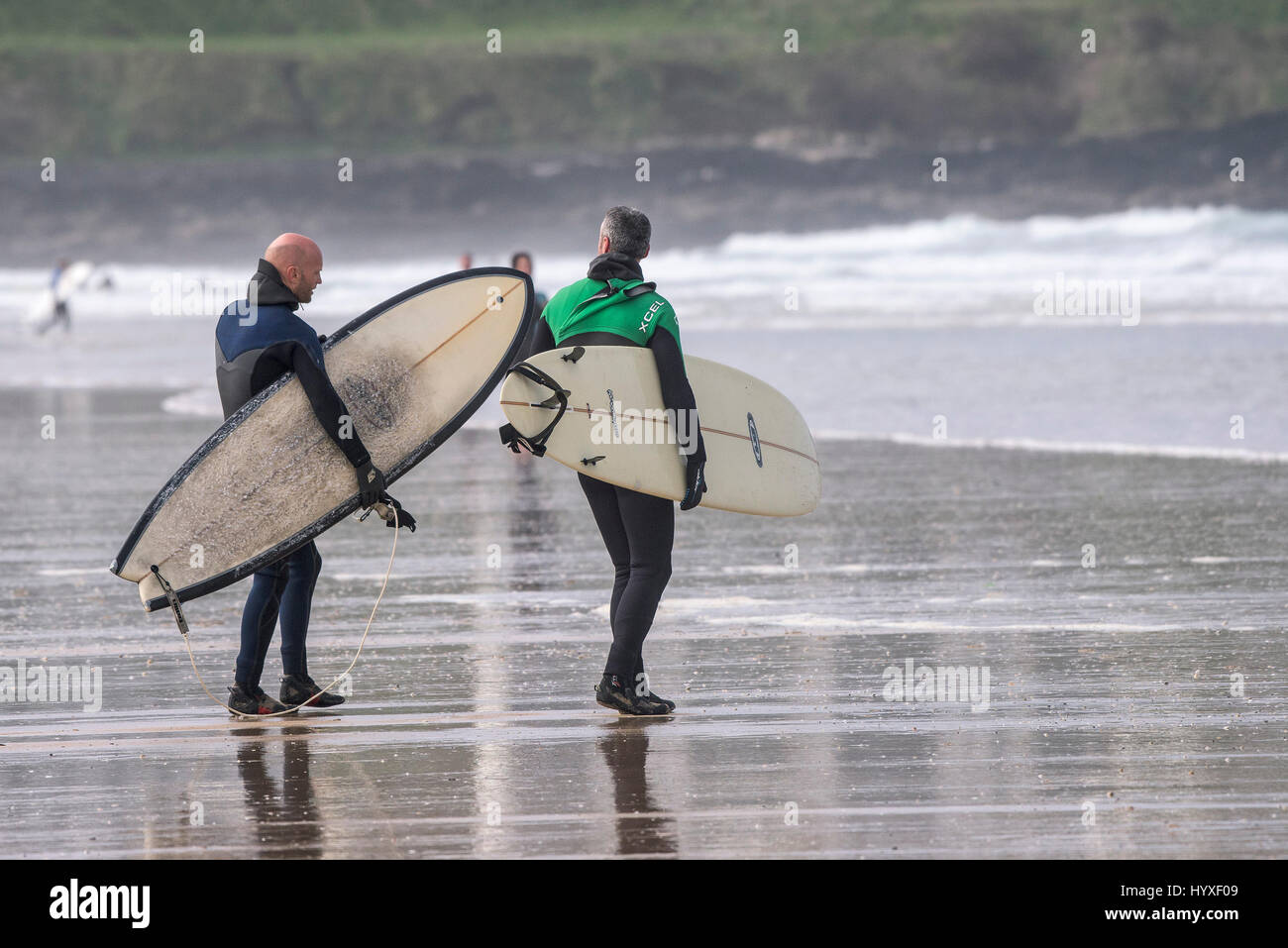 Two surfers carrying surfboards Surfing UK Cornwall Walking Watersport Leisure activity Lifestyle Recreation Friends - Stock Image
