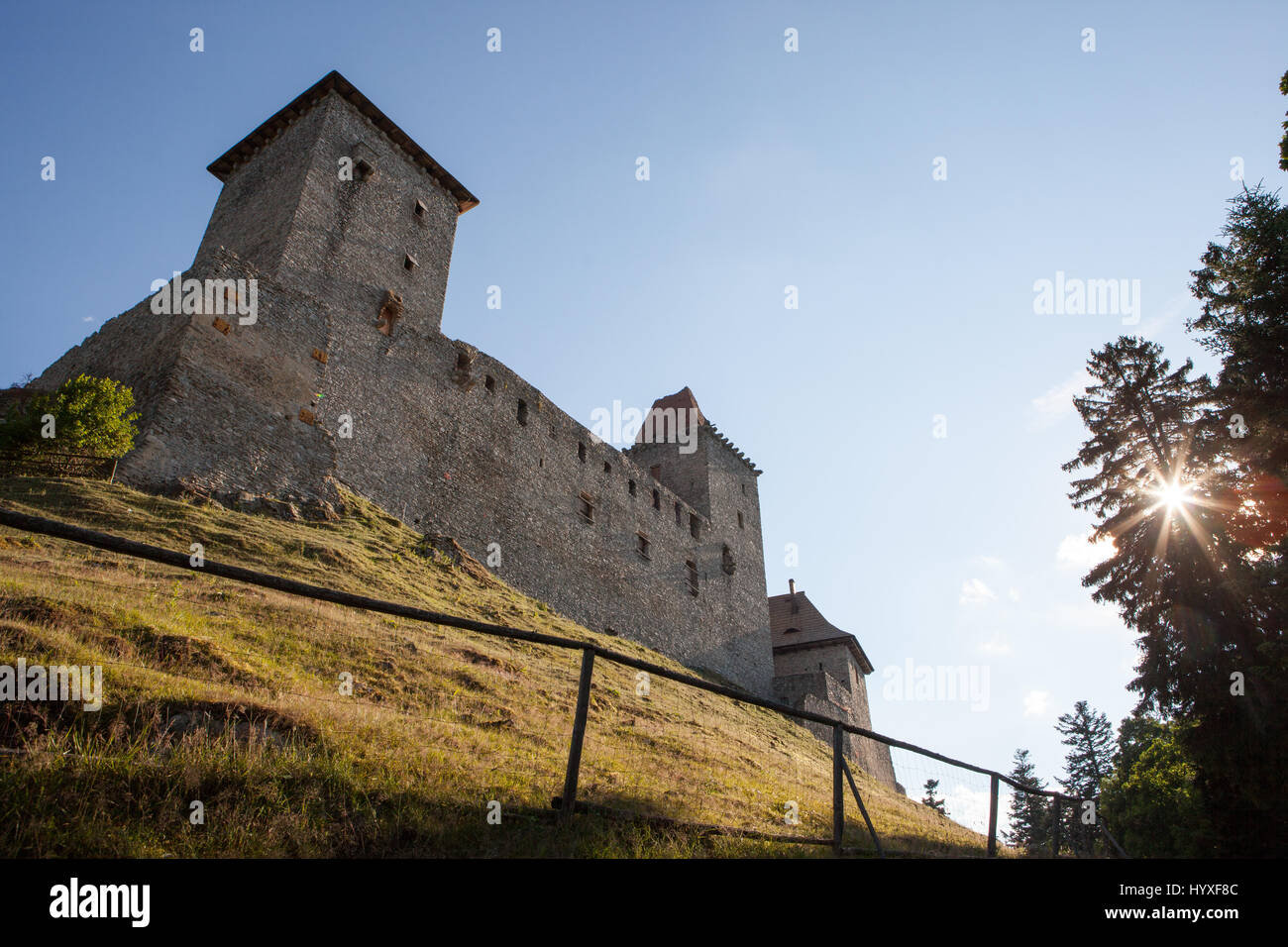 Castle Kasperk sits atop a hill as the sun bursts through the trees in the Bohemian forest of Sumava. - Stock Image