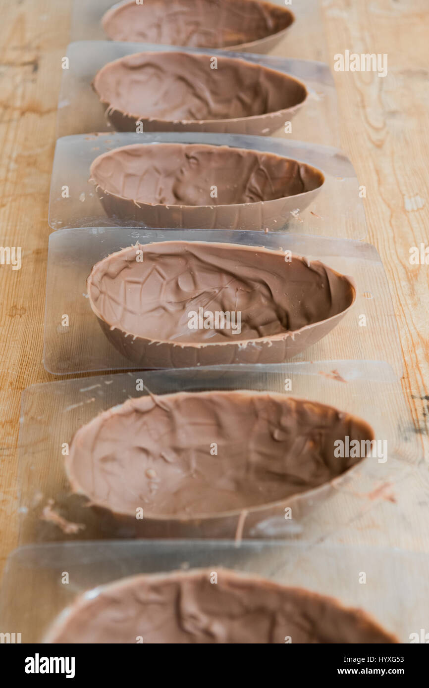Making handmade easter eggs - easter egg moulds with first layer of chocolate Stock Photo