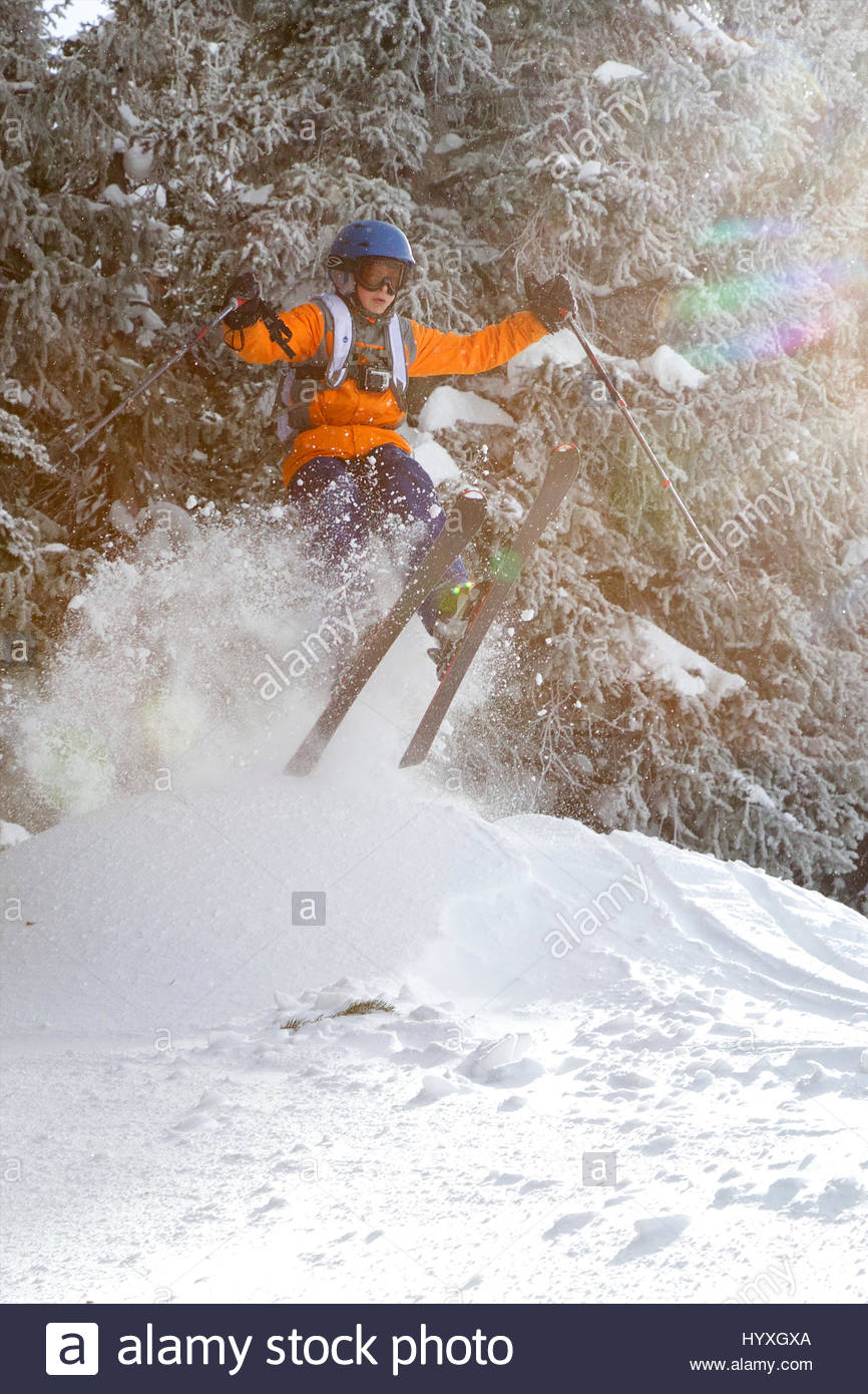 A young teen catches some air off a jump while skiing in Utah. - Stock Image