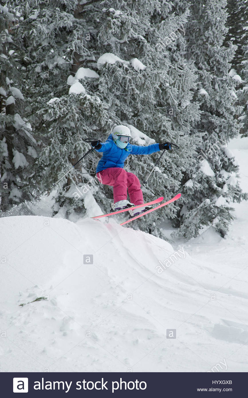 A young girl catches some air off a jump while skiing in Utah. - Stock Image