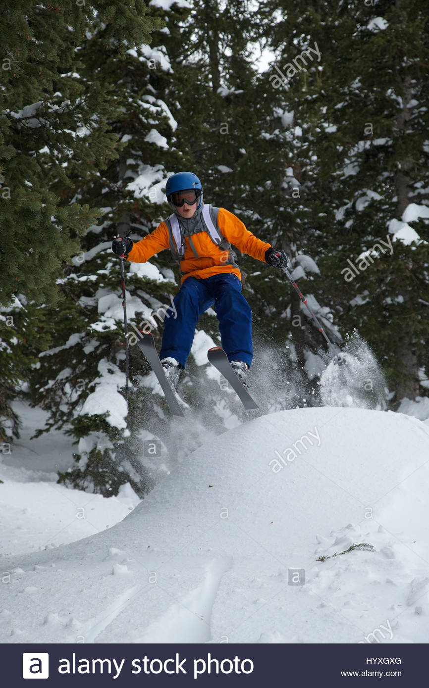 A young teenage boy gets some air off a jump while skiing in Utah. - Stock Image