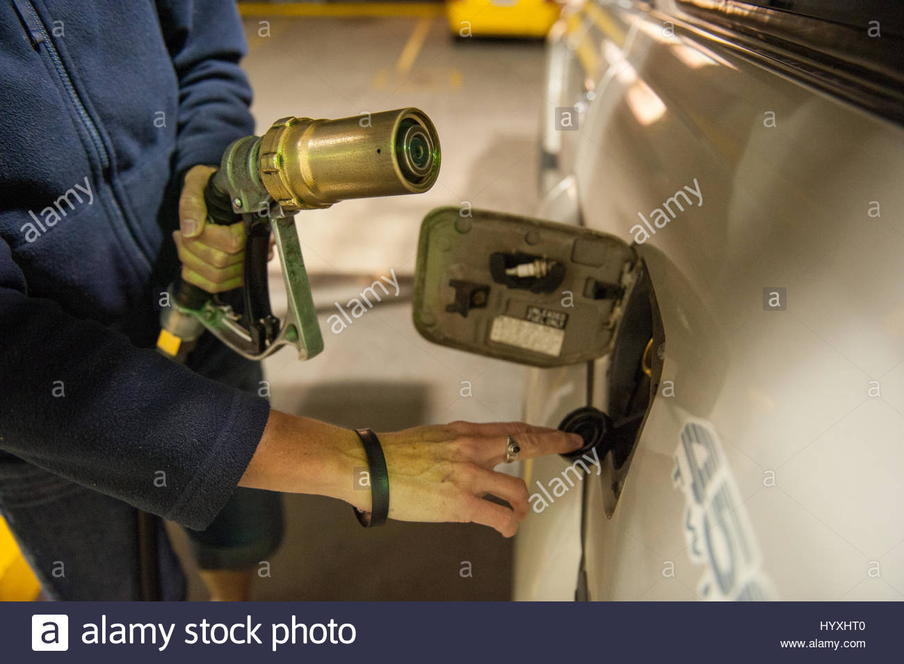 A woman fills up her vehicle with liquid natural gas. - Stock Image