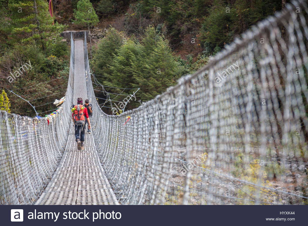 People trekking across a wire mesh footbridge over a river. Stock Photo