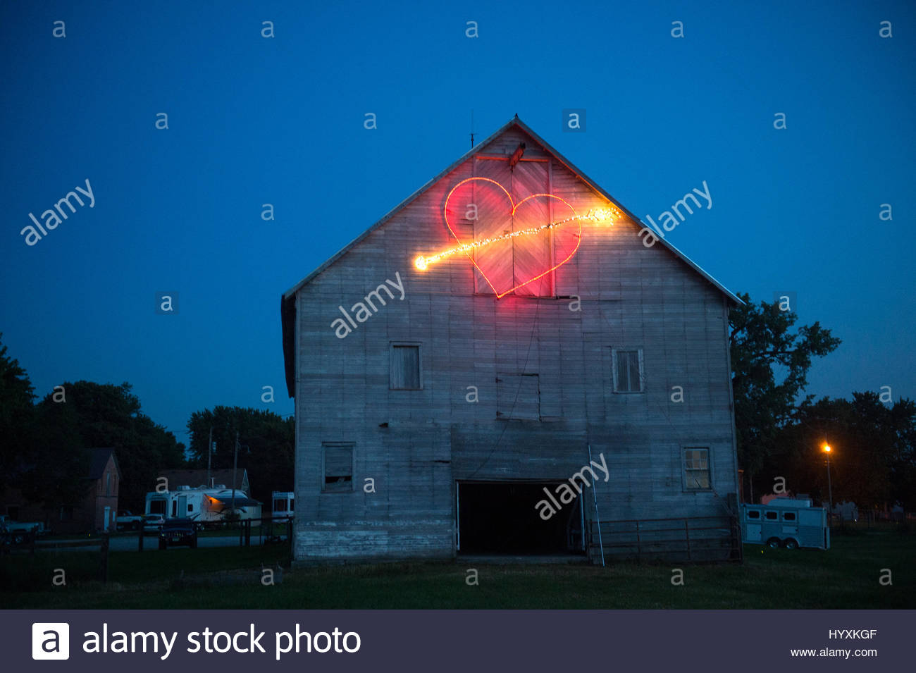 Heart shape made from light trail on the barn at a wedding reception. - Stock Image