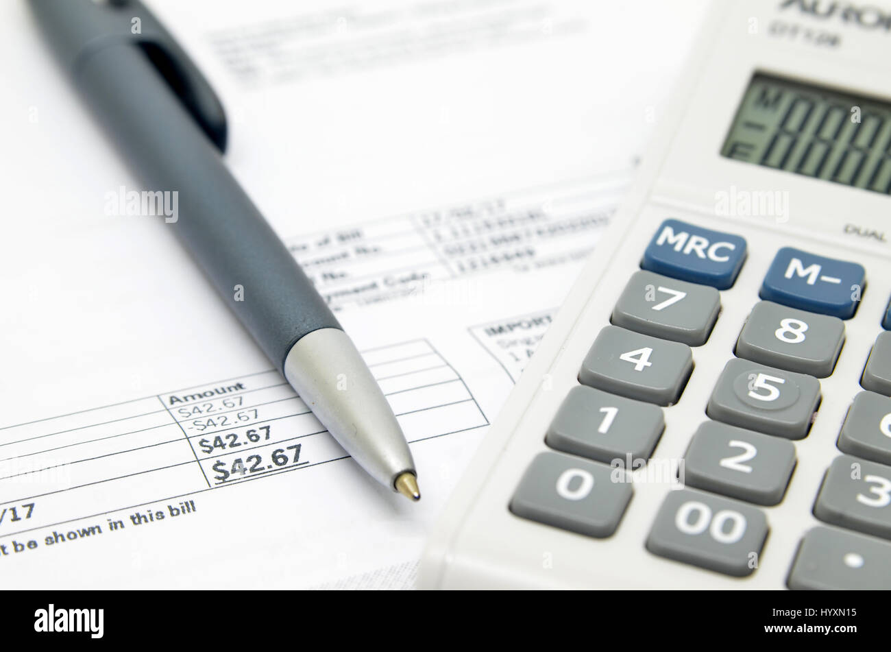 Pen on background of calculator and bill - Stock Image