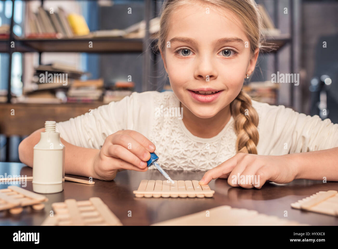 Smiling little girl handcrafting with ice cream sticks and glue - Stock Image