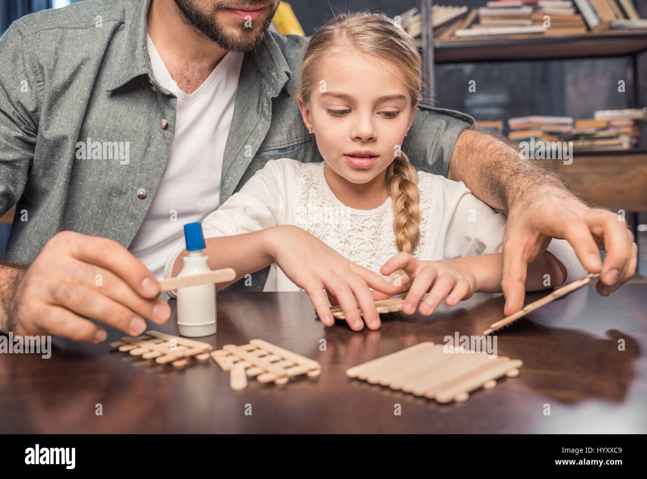 Father and daughter making ice cream wooden sticks figure - Stock Image
