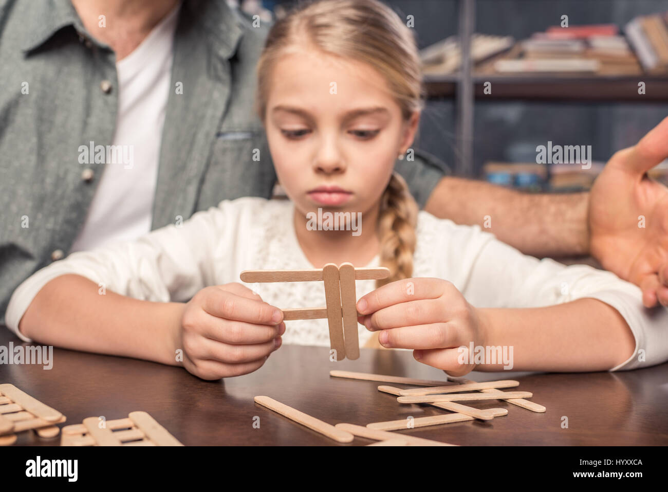 Concentrated little girl handcrafting with ice cream sticks - Stock Image
