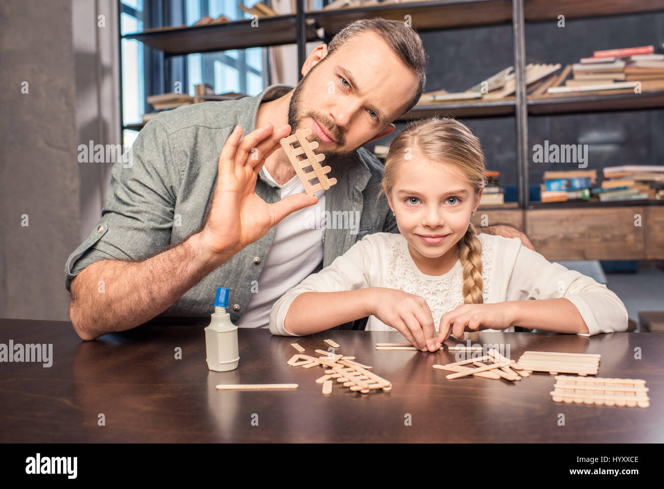 Father and daughter making ice cream wooden sticks figure Stock Photo