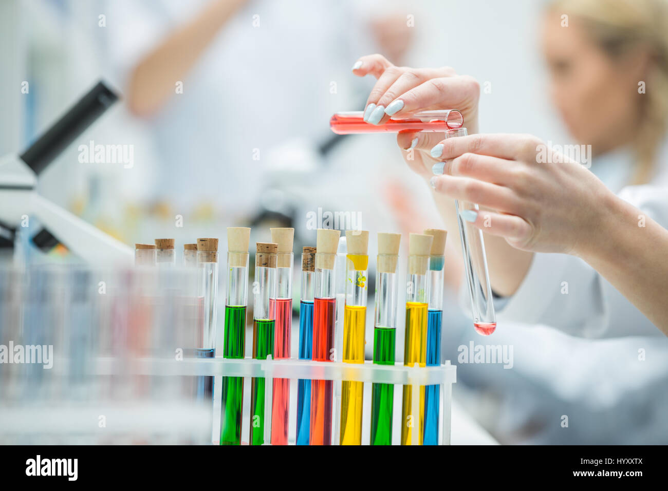 Close-up partial view of female scientist holding test tubes in chemical laboratory Stock Photo
