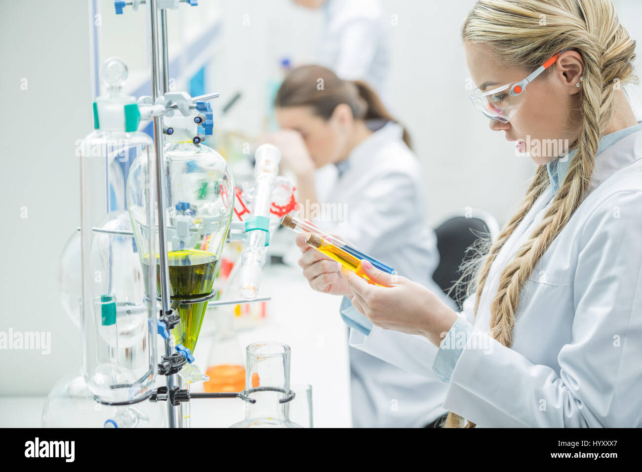 Young female scientist in protective glasses and lab coat looking at test tubes in laboratory Stock Photo