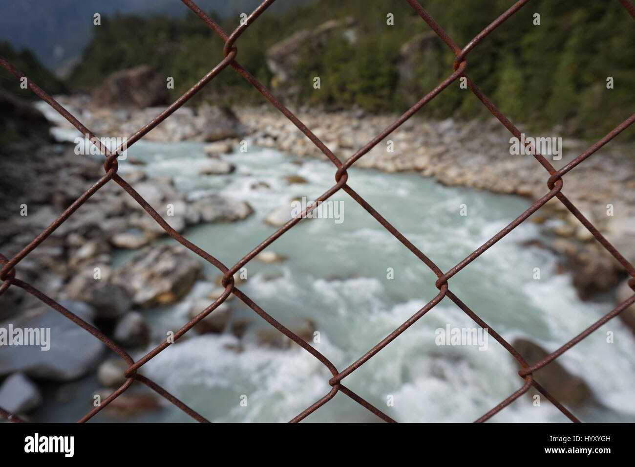 Looking out on the river through a wire fence - Stock Image