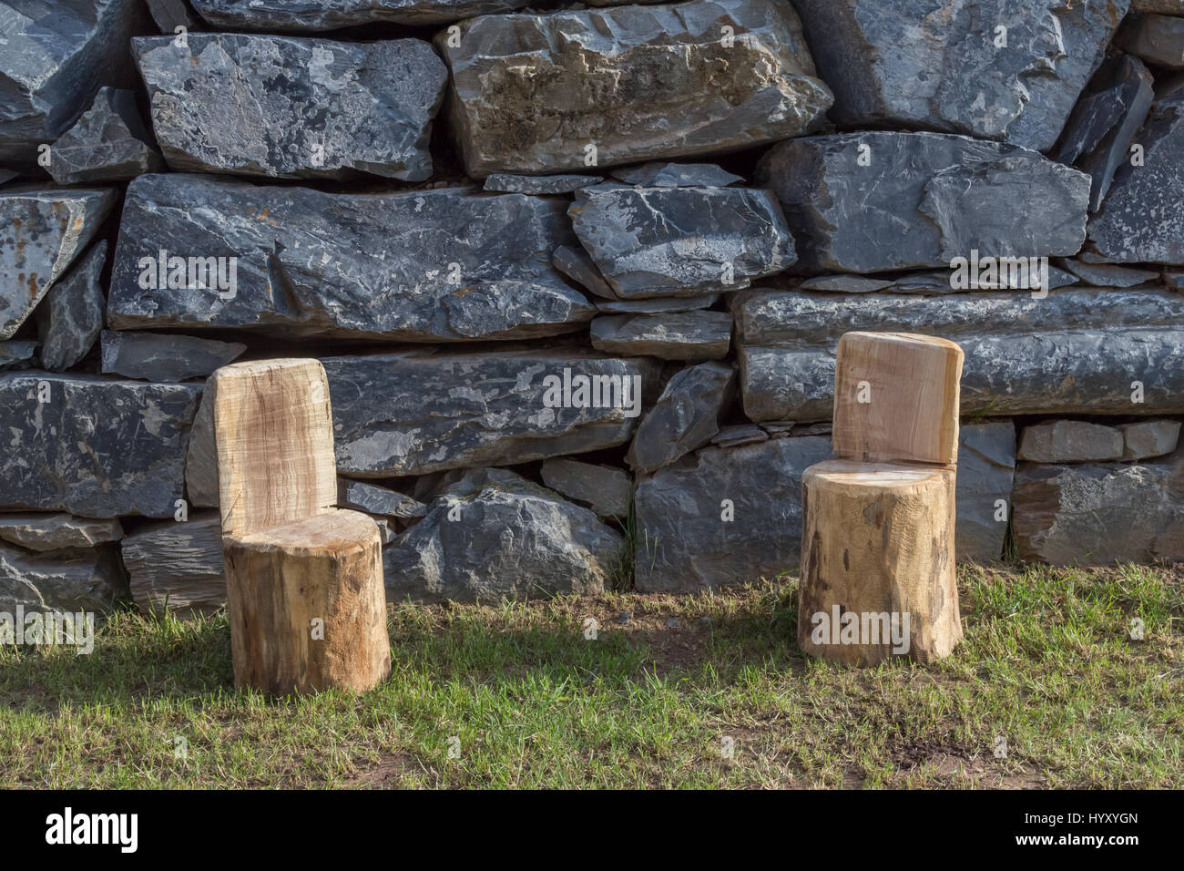 Two Handmade Wood Stools On The Garden Lawn With Different Natural Stones  Wall As Background