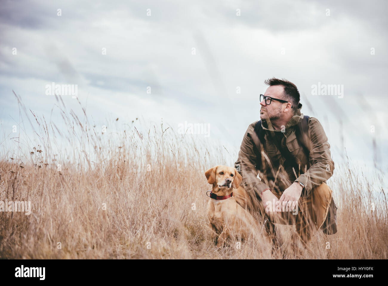 Man and dog resting in grassland - Stock Image