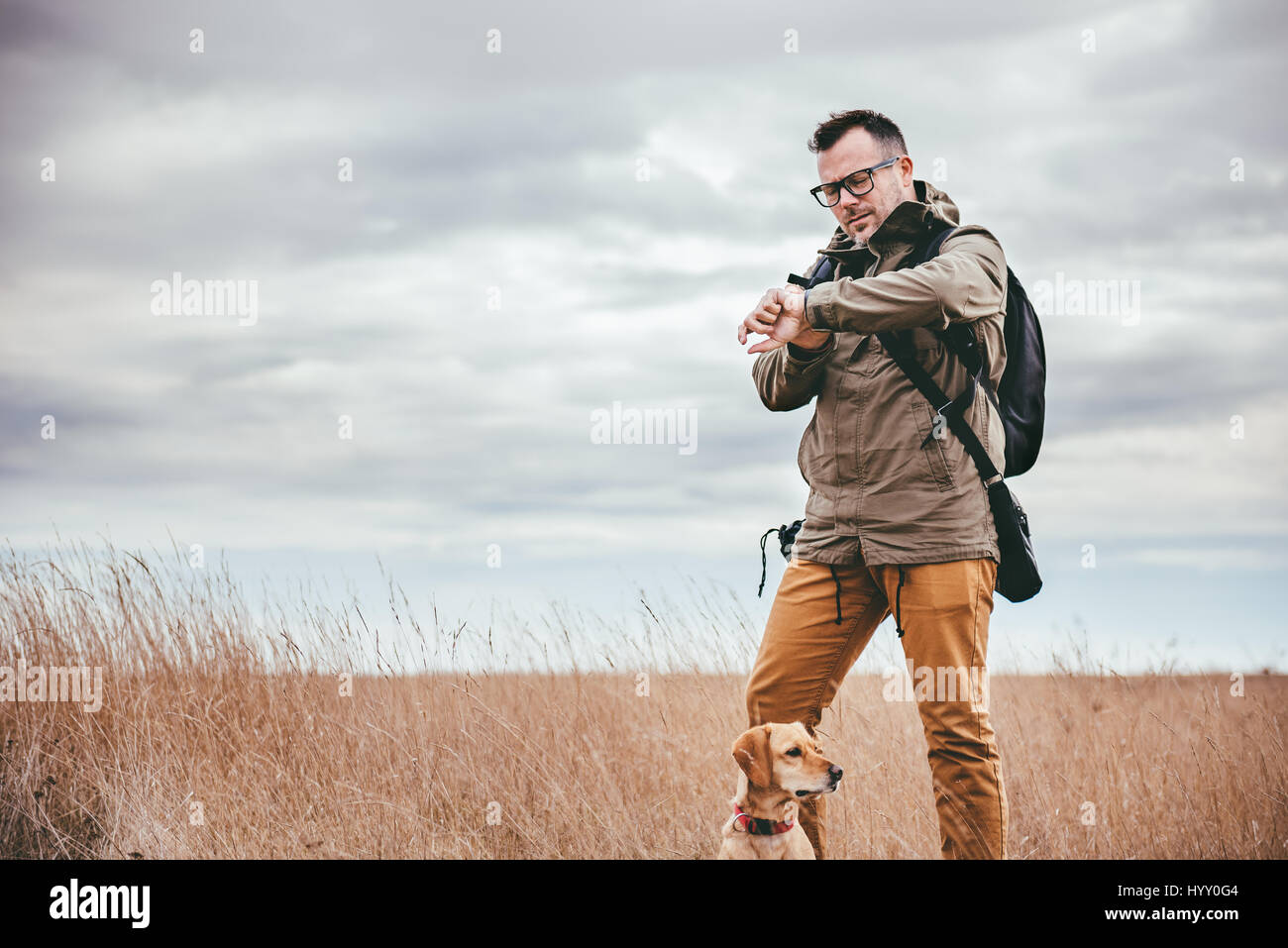 Hiker with dog standing in grassland and looking at watch - Stock Image
