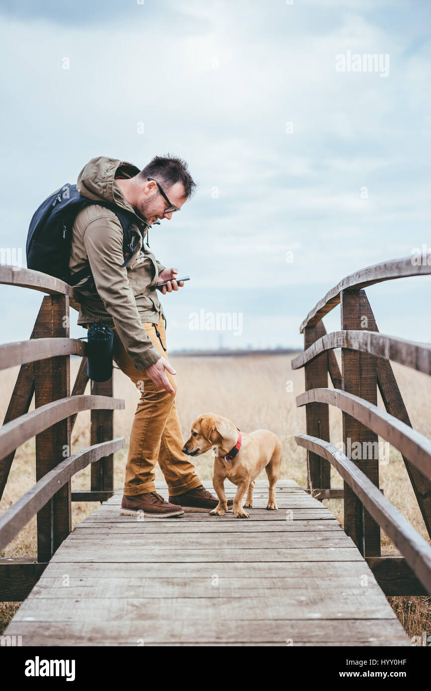 Hiker petting a dog on a wooden bridge - Stock Image
