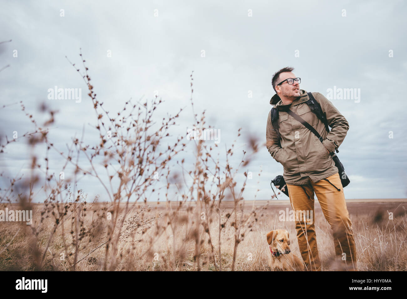 Hiker and dog walking in high grass on a cloudy day Stock Photo