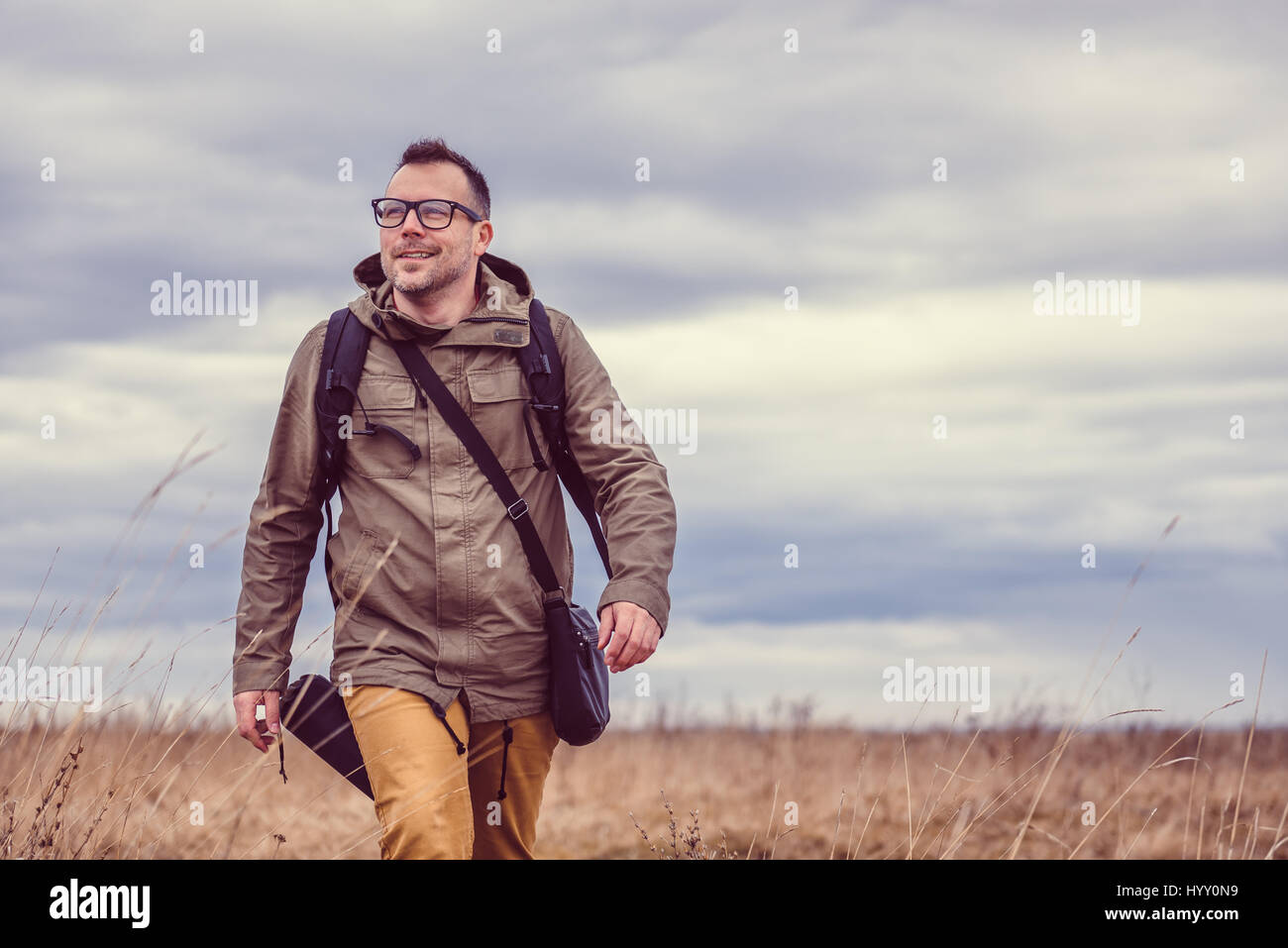 Hiker walking in grassland on a cloudy day - Stock Image