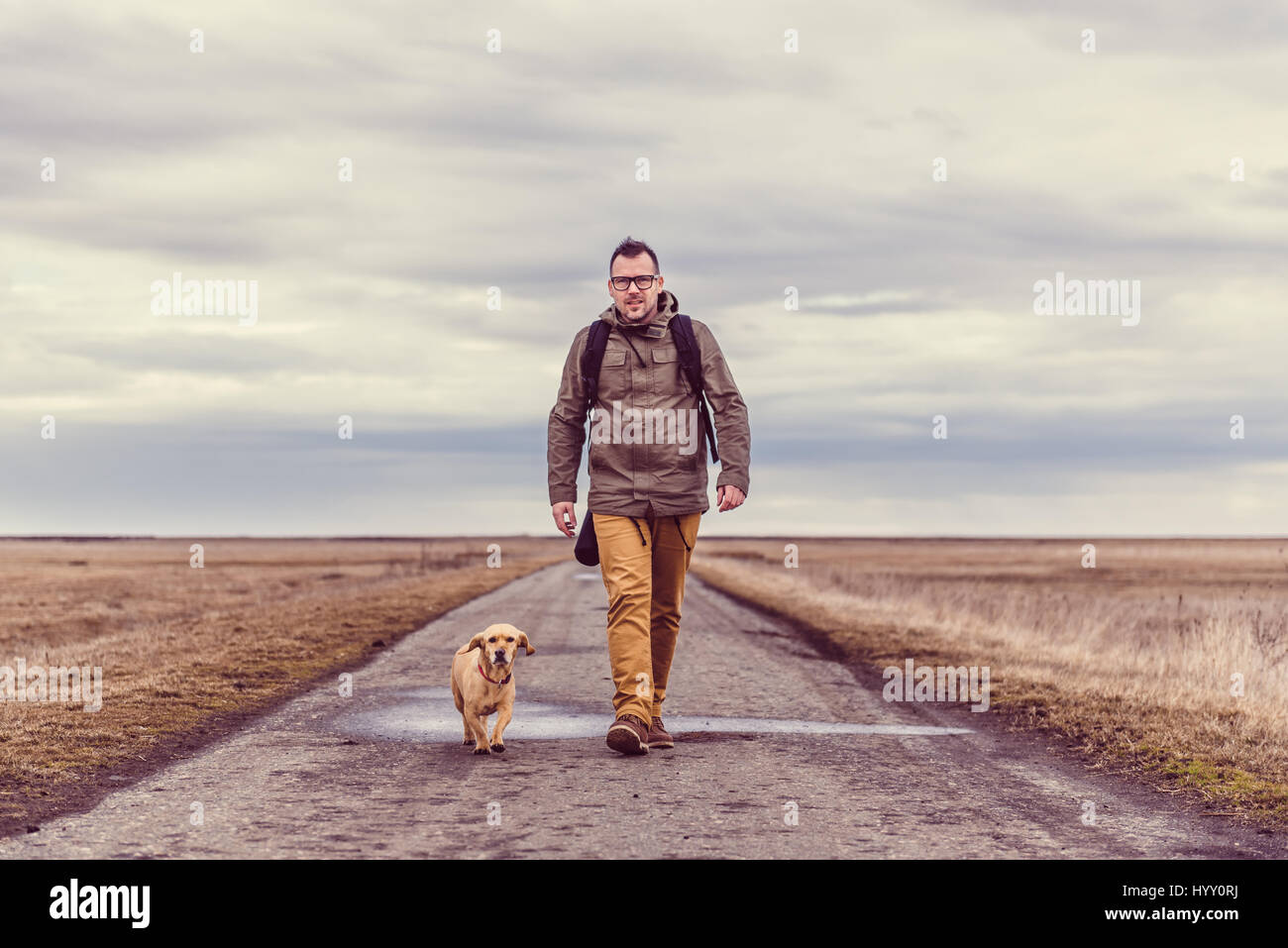 Hiker and dog walking down a road on a cloudy day - Stock Image