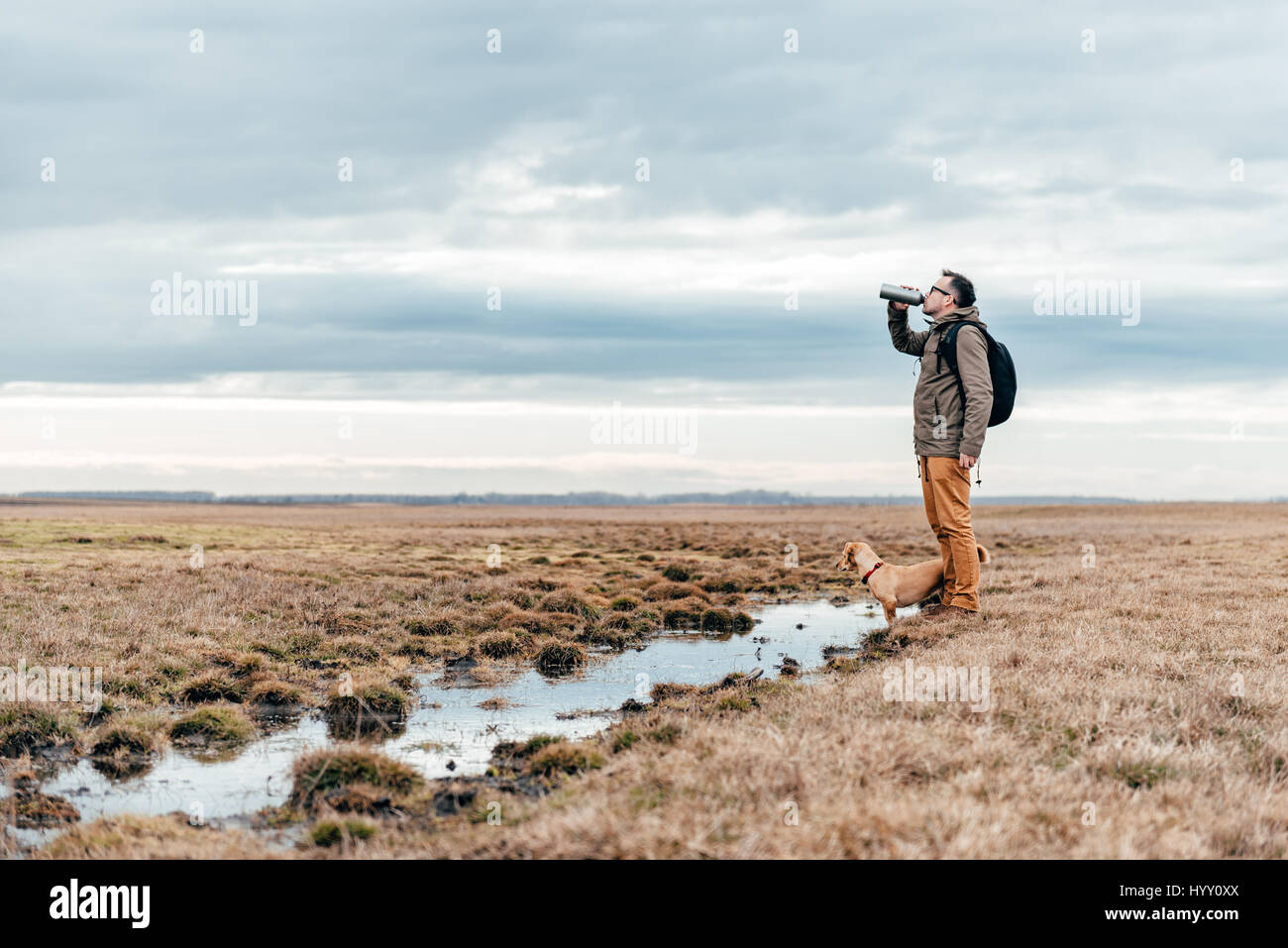 Hiker and dog standing by the pond in grassland on a cloudy day and drinking water - Stock Image