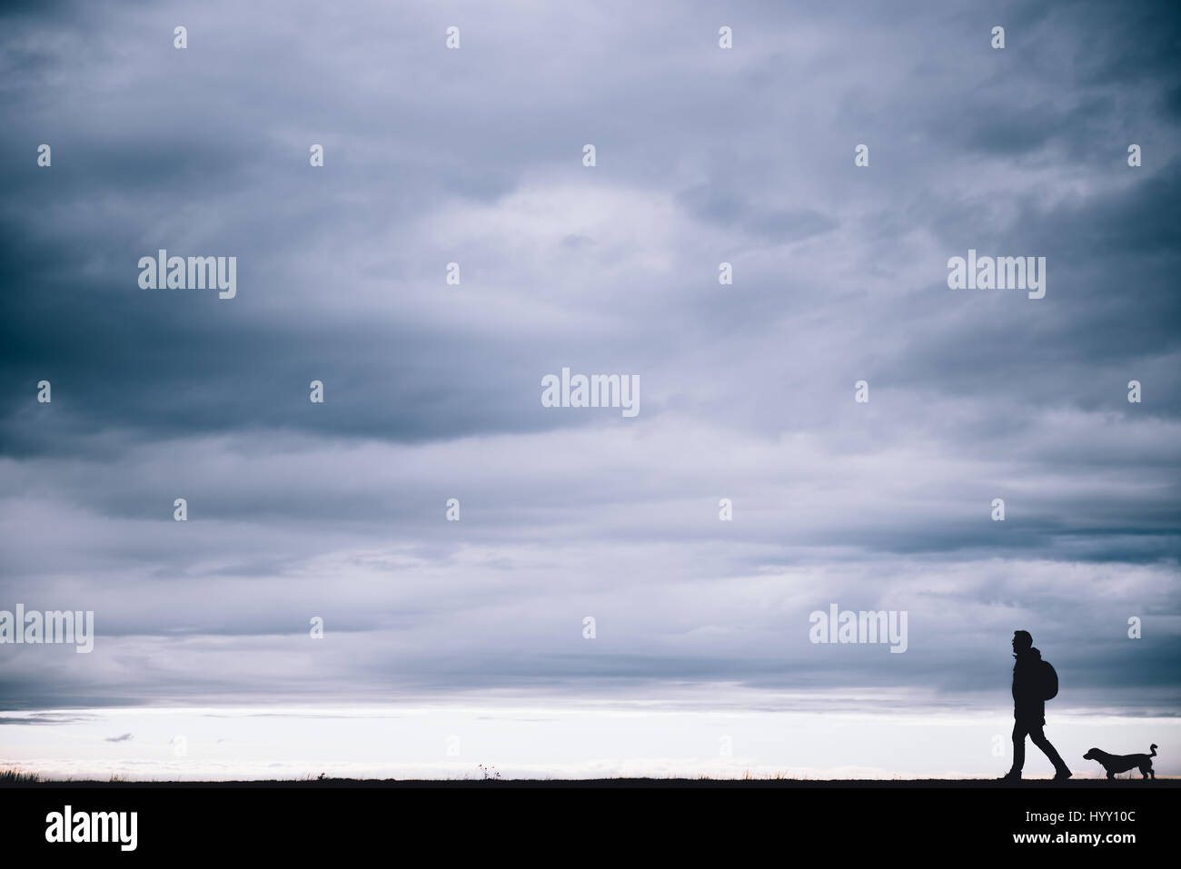 Silhouette of hiker and dog walking together - Stock Image