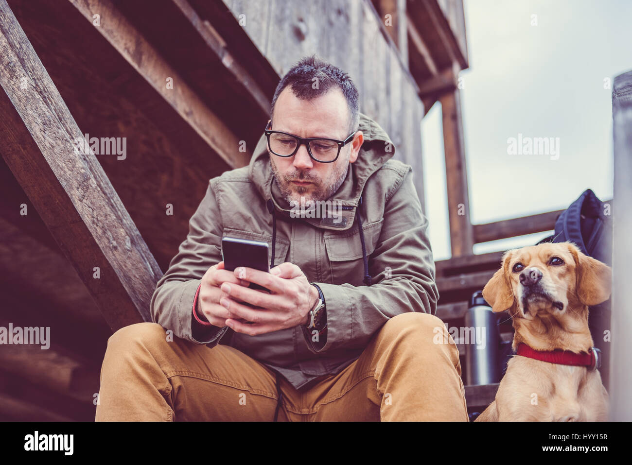 Hiker sitting on the stairs of hikers rest cabin with a dog and using smart phone Stock Photo