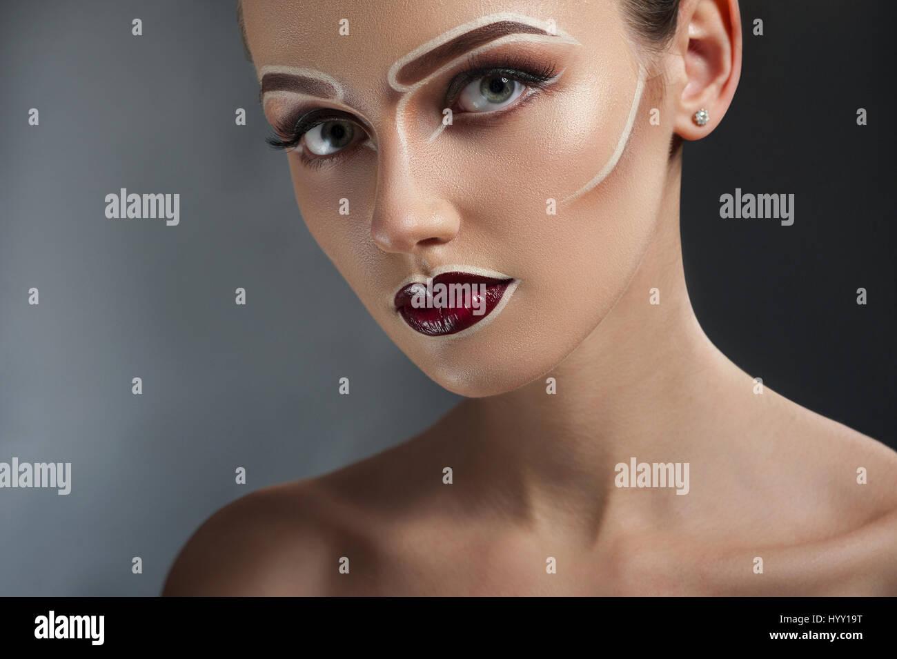 Hypnotizing depth. Closeup portrait of a gorgeous woman wearing artistic pop art makeup in brown tones - Stock Image