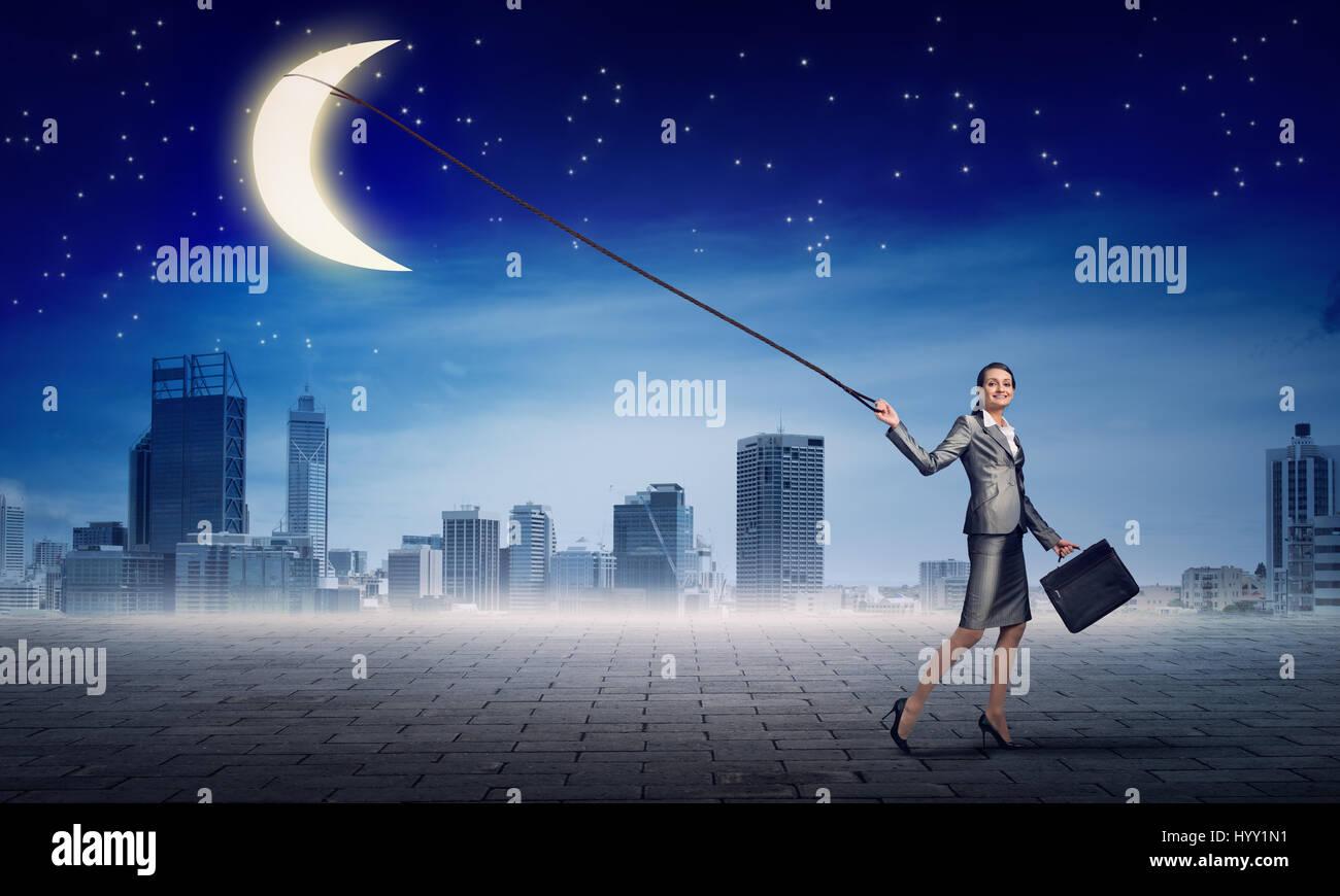 Woman catch moon - Stock Image