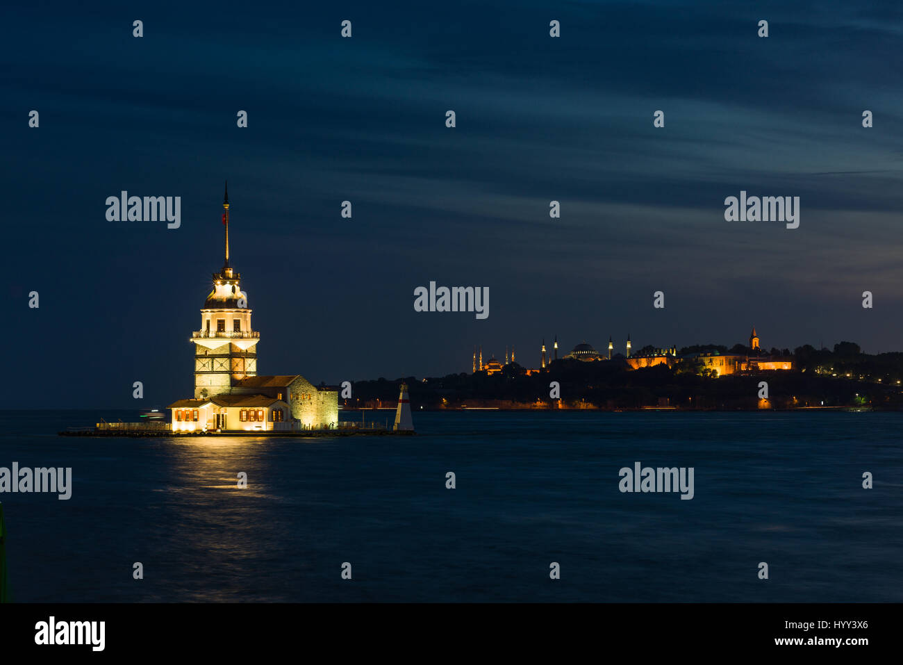 Maidens Tower (Kiz Kulesi) and Golden Horn lit up in evening light, Istanbul - Stock Image