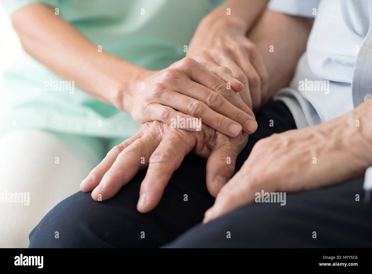 Care worker holding senior man's hands. - Stock Image