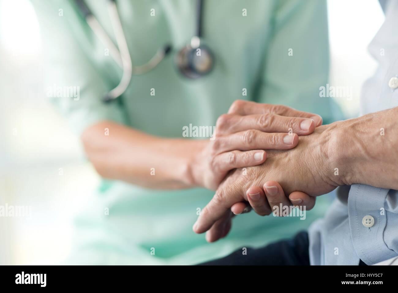 Care worker holding senior man's hand. - Stock Image
