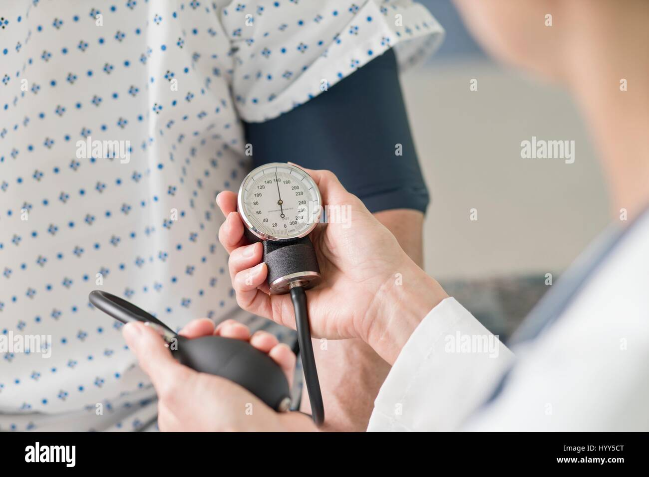 Doctor taking patient's blood pressure. - Stock Image