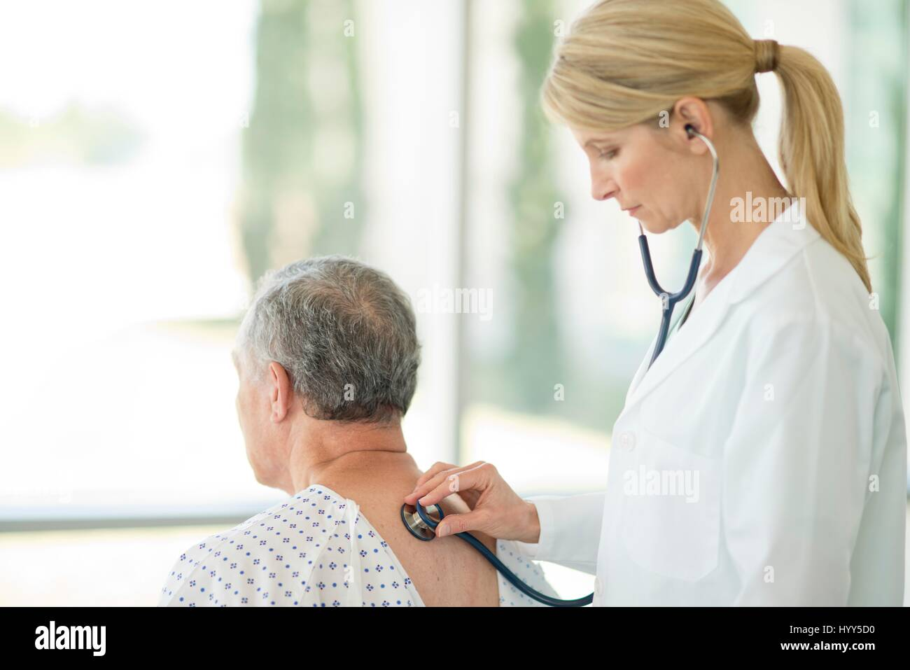 Female doctor using stethoscope on male patient. - Stock Image