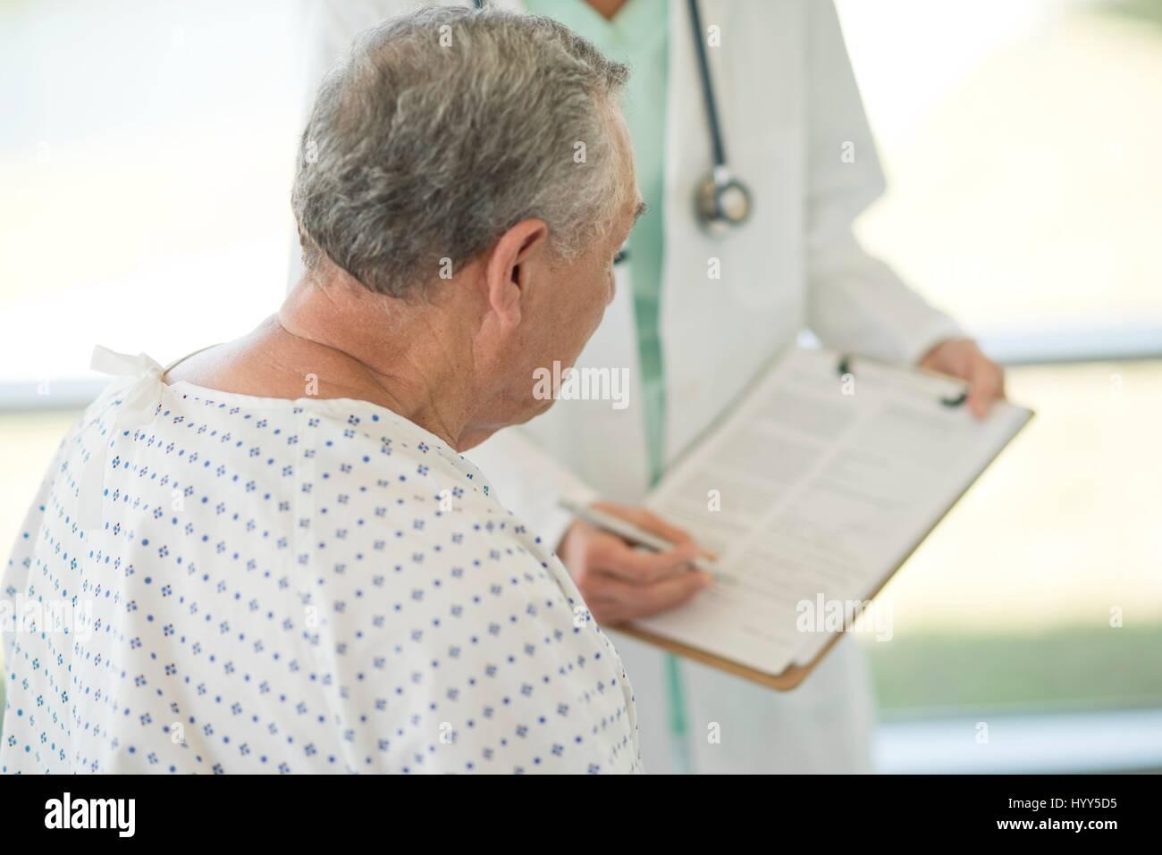 Senior man looking at medical notes in hospital. - Stock Image