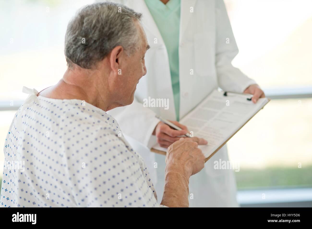 Senior man pointing at medical notes in hospital. - Stock Image
