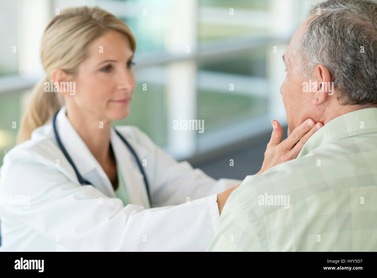Female doctor touching senior man's neck. - Stock Image