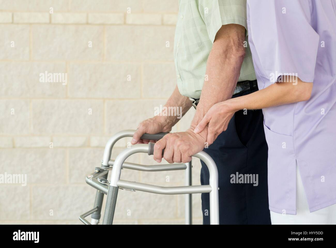 Senior man using walking support frame. - Stock Image