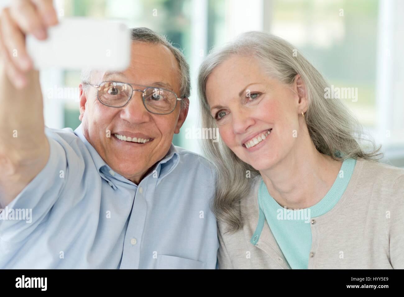 Portrait of senior couple taking selfie on phone. - Stock Image