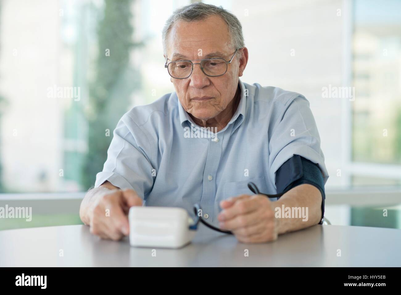 Senior man taking his own blood pressure. - Stock Image