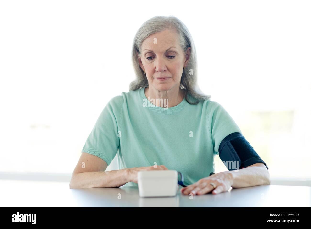 Senior woman taking her own blood pressure. Stock Photo
