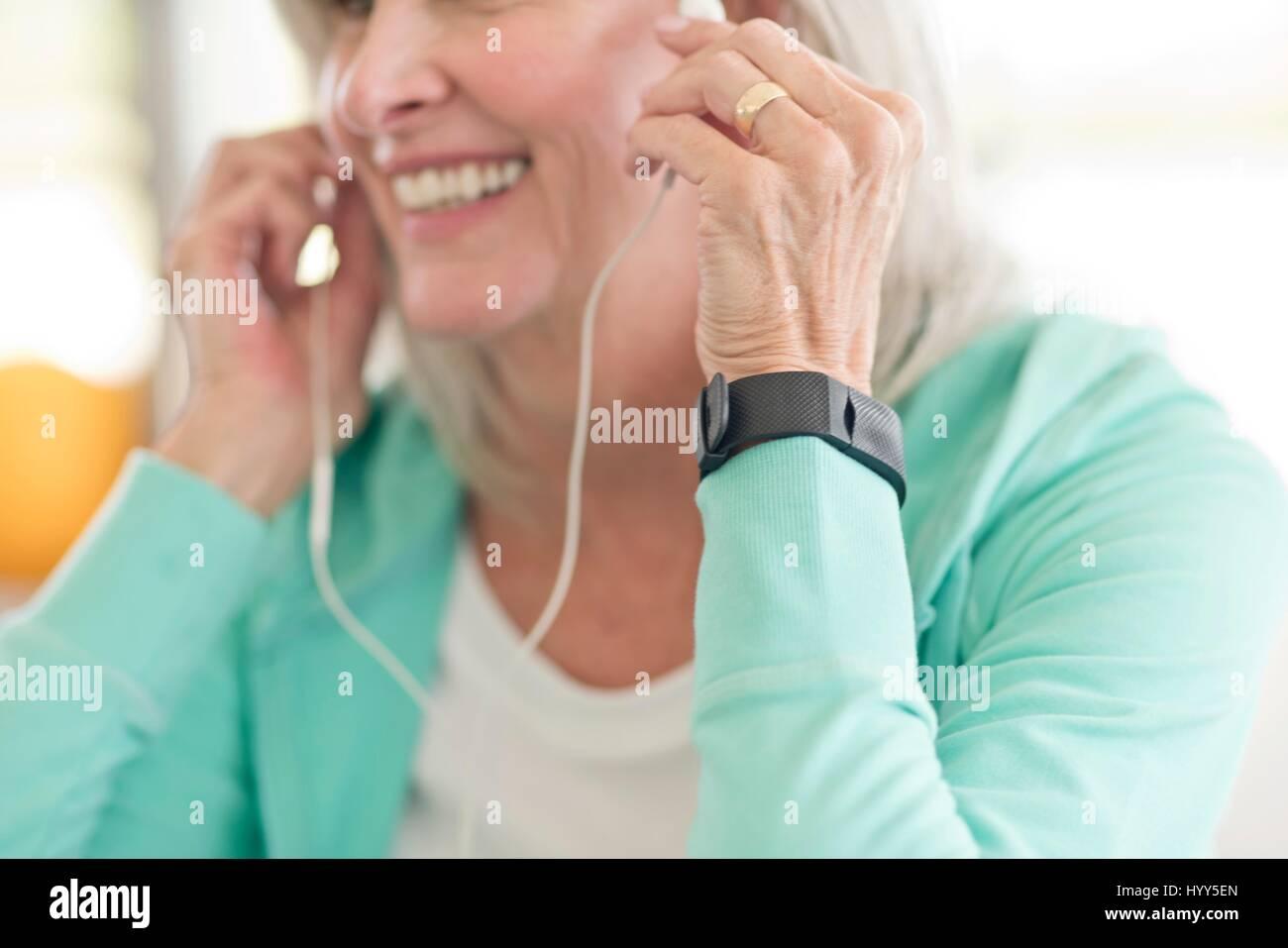 Senior woman listening to music on earphones. - Stock Image