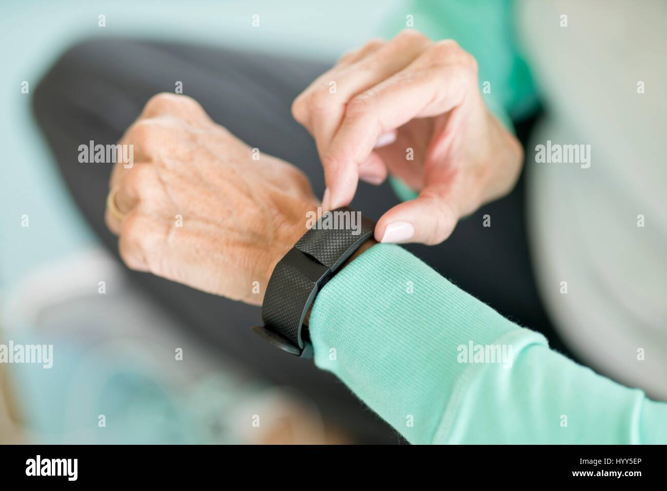 Senior woman using fitness tracker on wrist. - Stock Image