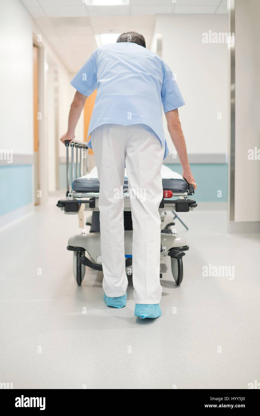 Nurse orderly pushing bed down corridor. - Stock Image