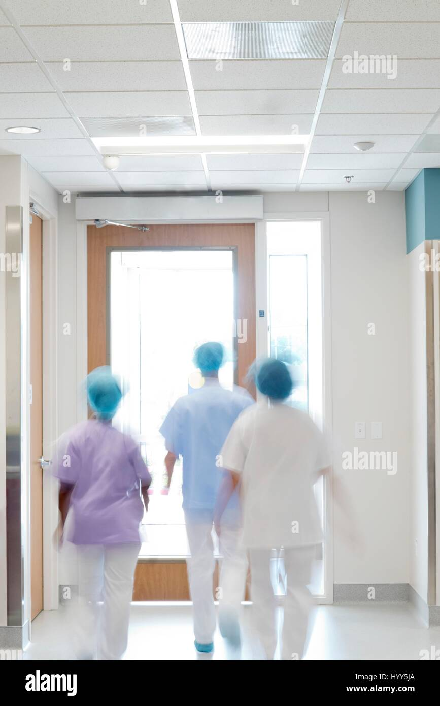 Medical staff walking down hospital corridor. - Stock Image