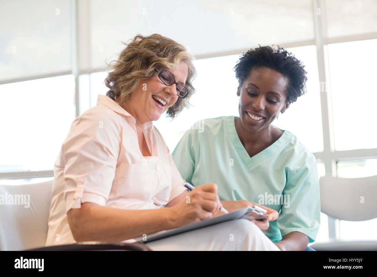 Mature woman filling out form with nurse, smiling. - Stock Image