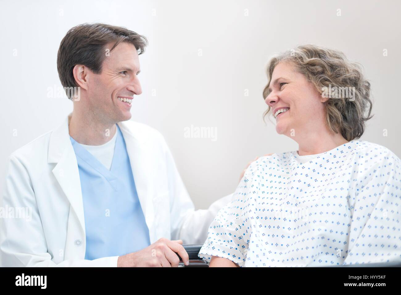 Male doctor smiling at mature female patient. - Stock Image