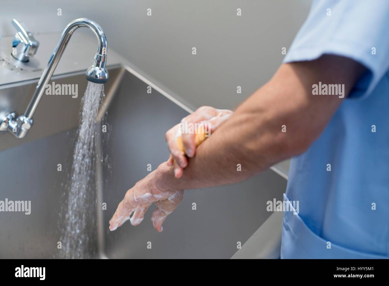 Doctor cleaning hands with soap and water in hospital. - Stock Image