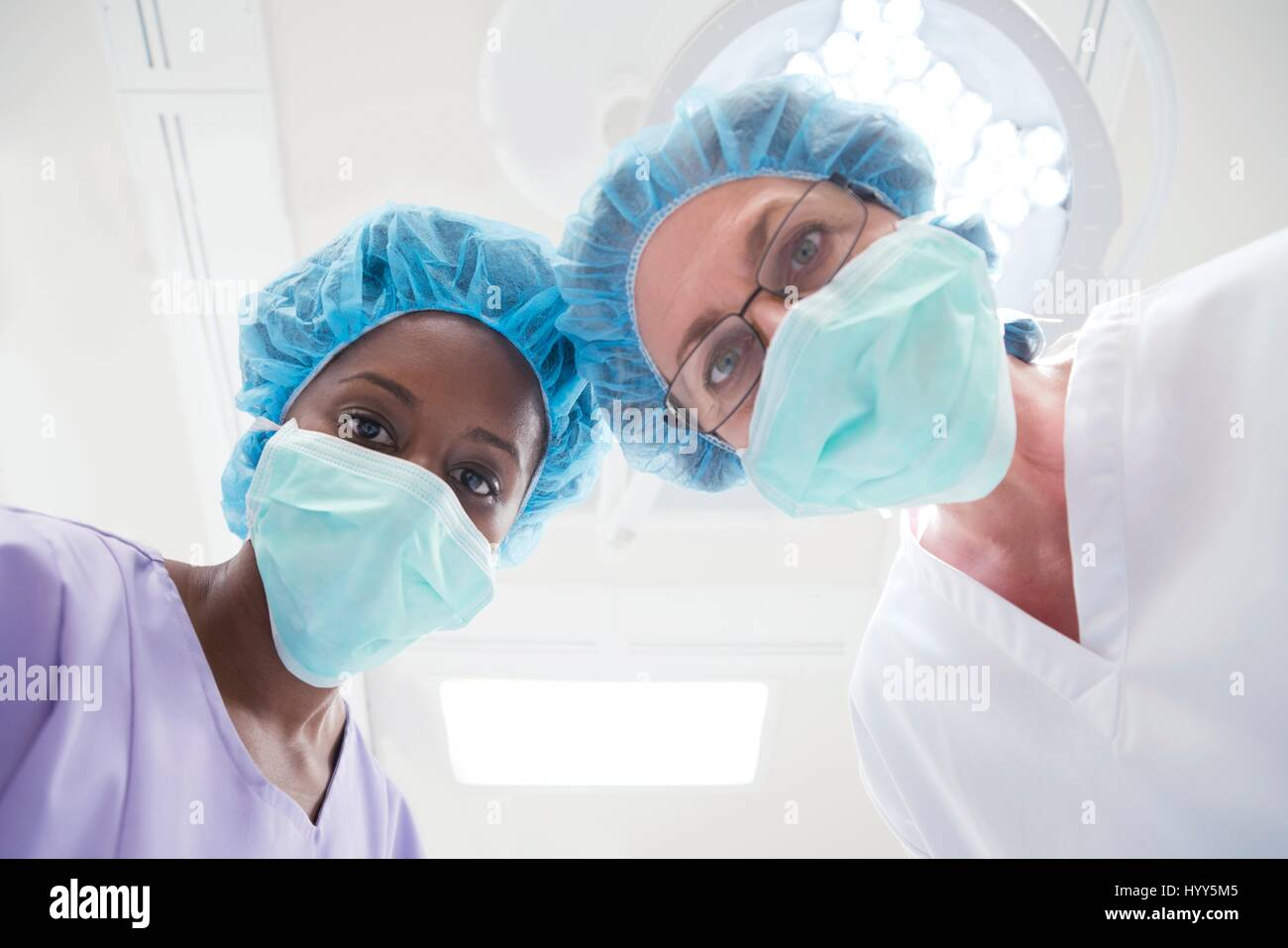 Two female surgeons looking towards camera, personal perspective. - Stock Image