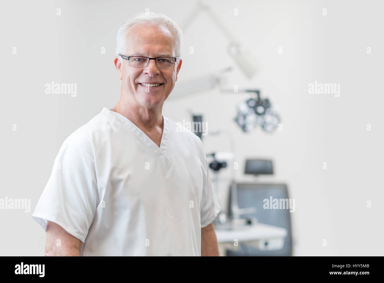 Senior male doctor dentist towards camera, portrait. - Stock Image